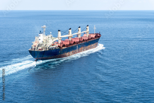 A old bulk carrier or bulker sails in the sea to trade around the world Wallpaper Mural