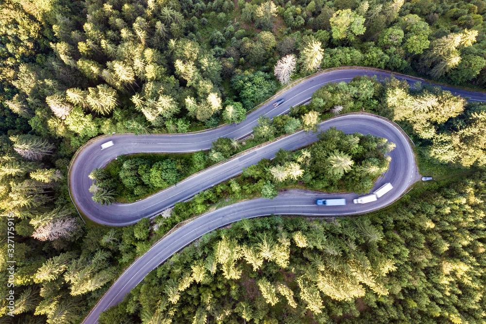 Fototapeta Aerial view of winding road in high mountain pass trough dense green pine woods.