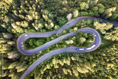 Obraz Aerial view of winding road in high mountain pass trough dense green pine woods. - fototapety do salonu