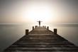 Leinwandbild Motiv Person steht mit offenen Armen bei Sonnenuntergang am Steg