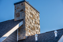 Large Stone Cladding Covered Masonry Chimney On Top Of A Asphalt Roof At A New USA Residential Construction Project