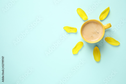 Cup of morning coffee and tulip petals on light blue background, flat lay Poster Mural XXL