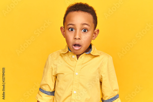 Fototapety, obrazy: Omg, wow. Emotional astonishing cute dark skinned child opening mouth and widening eyes watching something shocking, receiving intriguing news or gossip, staring at camera in full disbelief