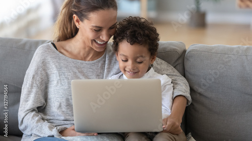 Smiling mother with African American son using laptop at home