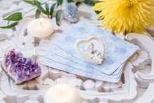 Deck With Divination Homemade Angel Cards On Bright White Table, Surrounded With Semi Precious Stones Crystals And Candles. Selective Focus On Cute Angel Figurine.