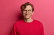 Dreamy handsome man with pleased expression, focused aside with delighted expression, tender smile, imagines first date, wears round spectacles and red jumper, has happy look, isolated on pink