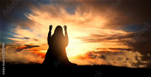 Photo silhouette of a Muslim woman praying at sunset