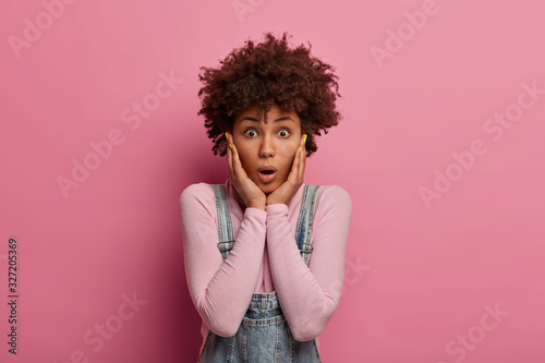 Portrait of astonished curly woman grabs face and stares with bugged eyes, gossips about something amazing, dressed casually, poses against pink background, being anxious about awful accident Canvas Print