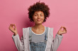 Leinwanddruck Bild - Portrait of relieved determined dark skinned woman meditates with closed eyes, practices breathing exercise or yoga to calm down, stands in lotus pose, poses over pink background, makes zen gesture