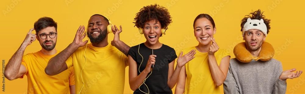 Fototapeta Overjoyed dark skinned woman sings song in smartphone, plump bearded man listens audio track in headphones, Asian female makes korean like sign, puzzled guy wears travel pillow around neck, sleep mask