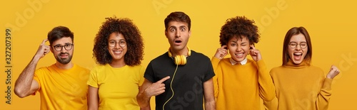 Surprised man indicates at himself, listens audio in headphones, Afro American woman plugs ears, puzzled male scratches head, positive female rejoices success and clenches fists Fototapet