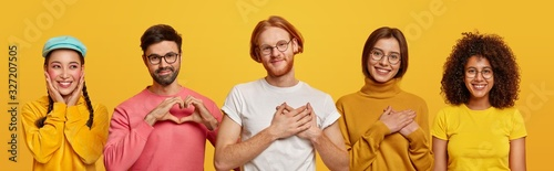 Obraz Group of people show love and sympathy, make heart gesture, express gratitude, being thankful for something, isolated over yellow studio background. Collage composition. Body language concept - fototapety do salonu