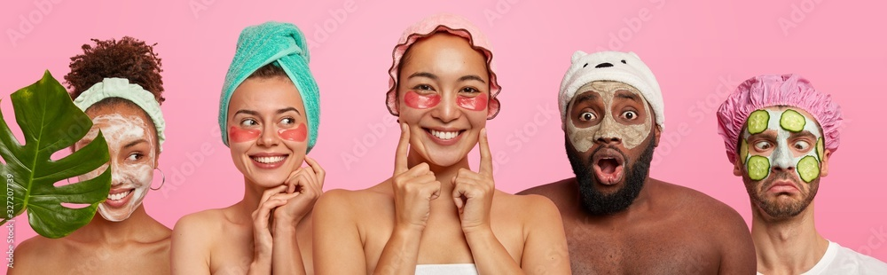 Fototapeta Photo of mixed race young women and man express different emotions, wear cosmetic masks and under eye patches, want to have healthy skin and well cared comlexion, pose bare shoulders indoor.