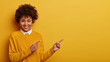 Cheerful pretty woman with Afro hair points at copy space, shows recommendation, suggests going this direction or promo, wears neat sweater, isolated over yellow background, makes good choice