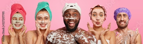 Fotografia Set of women and men enjoy pampering, wash body and face with foam, wear towels or bath caps on head, pose naked indoor, stand next to each other, isolated over pink background