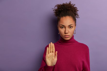 Pretty Serious Woman Pulls Palm Towards Camera, Show No Rejection Gesture, Refuses Or Says Hold On, Dressed In Casual Poloneck, Being Not Interested In Something, Tries To Calm Someone. Stop Here
