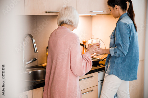Grandmother and adult granddaughter cooking dinner at home Fotobehang