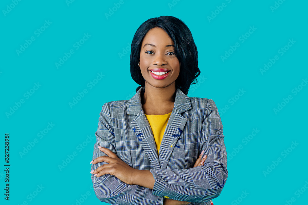 Fototapeta Portrait of a  happy smiling young woman in business jacket with arms crossed isolated on blue