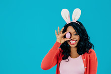 Portrait Of A Smiling Happy Young Woman Holding Easter Egg Over Eye And Bunny Ears, Isolated On Blue Background