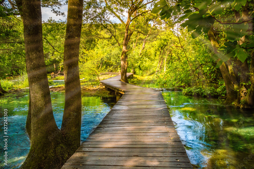 Wooden footpath over river in forest of Krka National Park, Croatia. Beautiful scene with trees, water and sunrays.