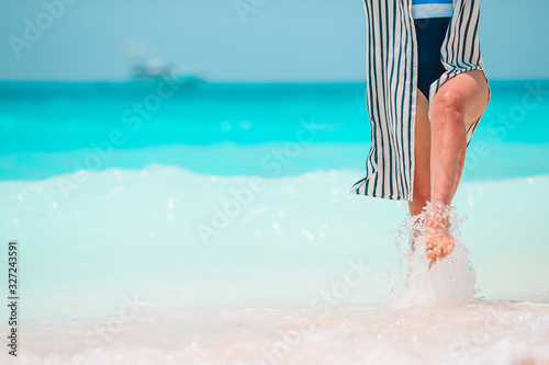 Woman's feet on the white sand beach in shallow water Fototapet