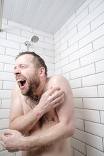 Funny Bearded Man Feels Shocked By Taking A Cold Shower, He Froze, Screams And Tries To Close His Body With Hands.