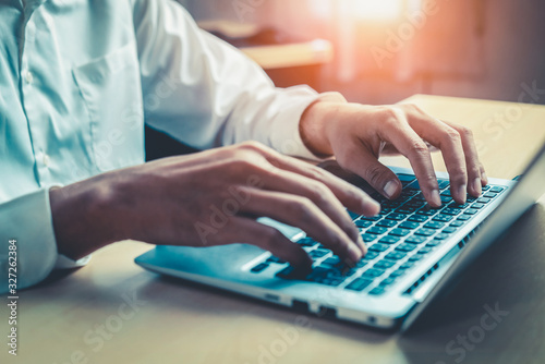 Fototapeta Businessman hand typing on computer keyboard of a laptop computer in office. Business and finance concept. obraz