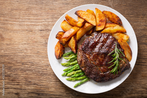 Fotografía plate of grilled steak with rosemary, asparagus and potato, top view