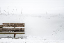A Wooden Bench In Snow