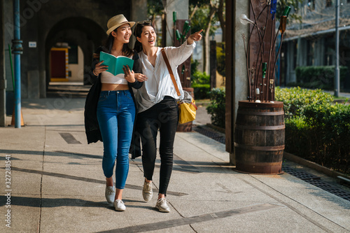 Photo two asian tourists sisters travel in little village in europe