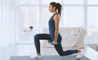 Slim Hispanic girl doing lunges with dumbbells at home, empty space