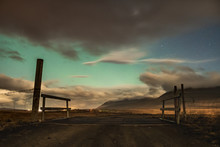 Aurora Borealis In Iceland Northern Lights Shining Through Gaps In Clouds Over Icelandic Landscape