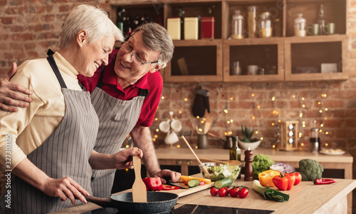 Fototapeta Happy Elderly Couple Embracing And Bonding While Cooking Dinner Together obraz