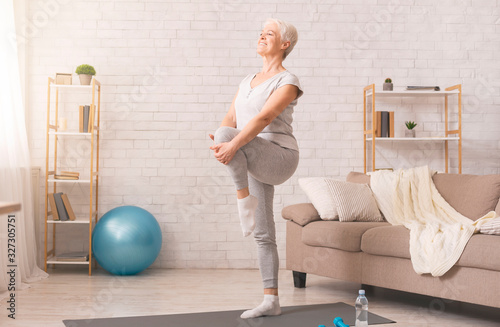 Foto Active senior woman doing legs exercise at home