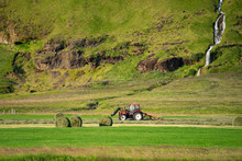Red Tractor Collecting Grass On Green Field With Beautiful River Going By The Mountain On Background
