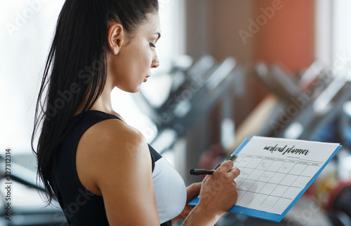 Fotografia Personal trainer with clipboard making workout plan in gym