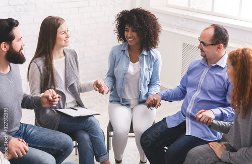 Fototapeta Young multi-cultural group of people holding hands during therapy session
