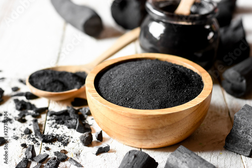 Black charcoal powder for facial mask and scrub, placed on a white wooden table, health and beauty concept Canvas Print