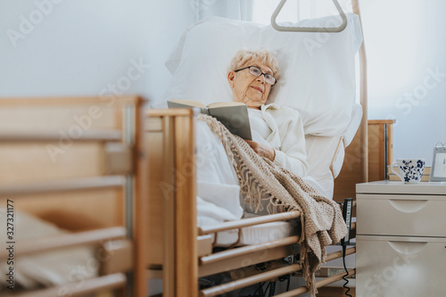 Sick senior woman lies in a hospital bed and reads a book Fototapet