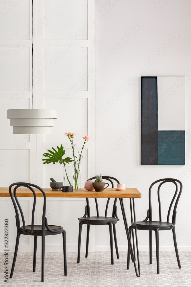 Fototapeta Elegant dining room interior with black wooden chairs and green plants