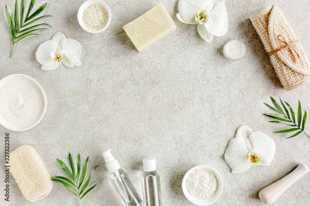Fototapeta Spa skincare concept. Natural/Organic spa cosmetics products, sea salt and tropic palm leaves on gray marble table from above. Spa background with a space for a text, flat lay, top view.