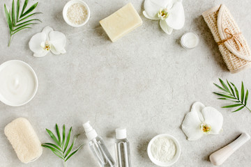 Spa skincare concept. Natural/Organic spa cosmetics products, sea salt and tropic palm leaves on gray marble table from above. Spa background with a space for a text, flat lay, top view.