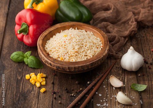 Wooden bowl with boiled long grain basmati rice with vegetables on wooden table background with sticks and paprika pepper with corn,garlic and basil Canvas Print
