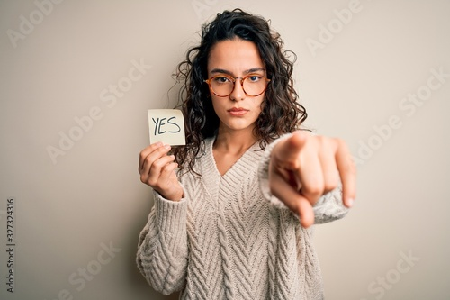 Young beautiful woman with curly hair holding reminder paper with yes word messa Canvas Print
