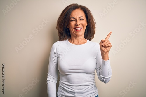 Fotografia, Obraz Middle age beautiful woman wearing casual t-shirt standing over isolated white background with a big smile on face, pointing with hand and finger to the side looking at the camera