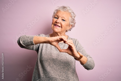 Obraz Senior beautiful woman wearing casual t-shirt standing over isolated pink background smiling in love doing heart symbol shape with hands. Romantic concept. - fototapety do salonu