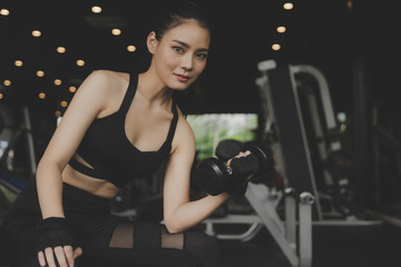 Fototapeta na wymiar athletic asian slim body woman smiling looking at camera and exercise with dumbbell in fitness gym in background, bodybuilder, healthy lifestyle, exercise fitness, workout and sport training concept