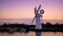 Thurne Mill In The Norfolk Broads With A Pink Sunrise Reflecting In The Water And Boats Moored Alongside