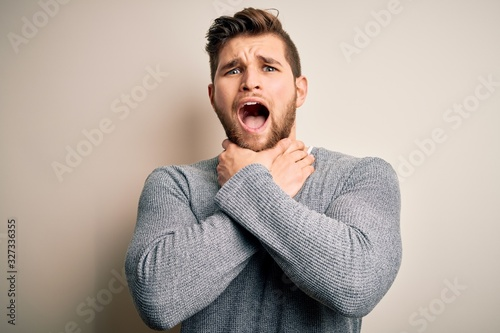 Photo Young handsome blond man with beard and blue eyes wearing casual sweater shouting and suffocate because painful strangle