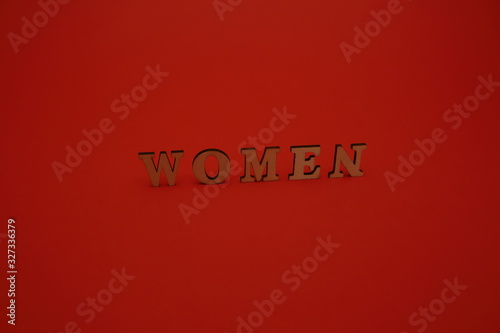 Photo Word WOMEN mand of wooden letters standing a bit aslant isolated on red backgrou